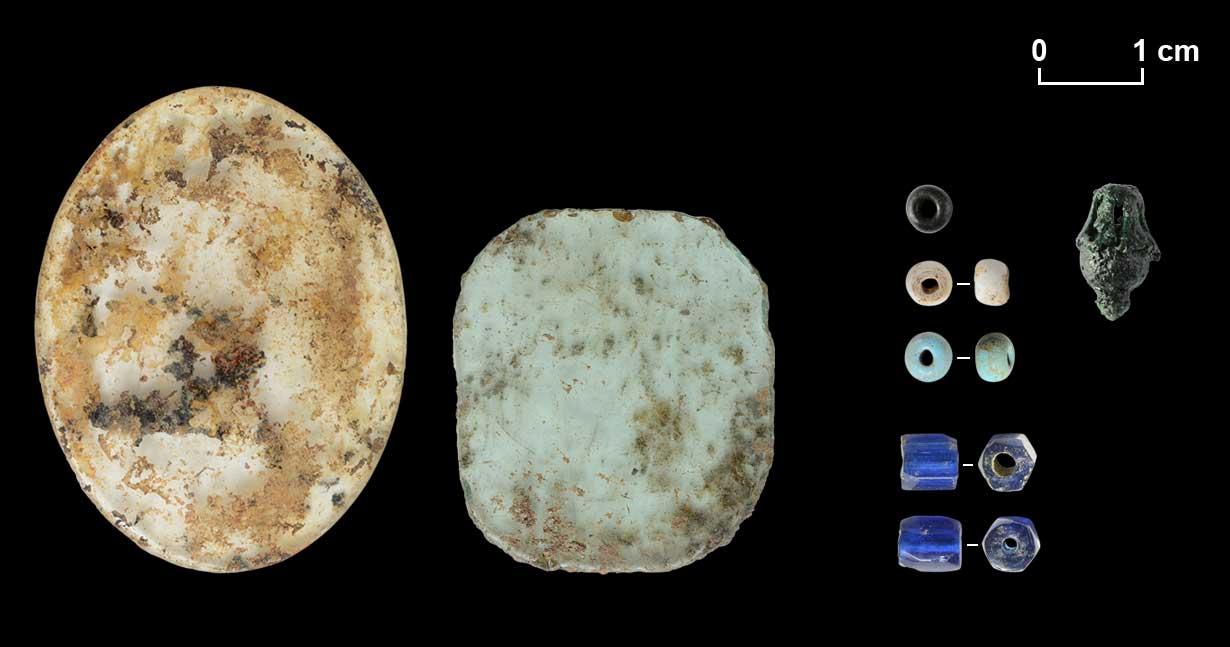 Zwei Glasscheiben von Schmuckstücken. Drei Rocailles und zwei gesprengte Perlen mit sechseckigem Querschnitt. Berlocke.